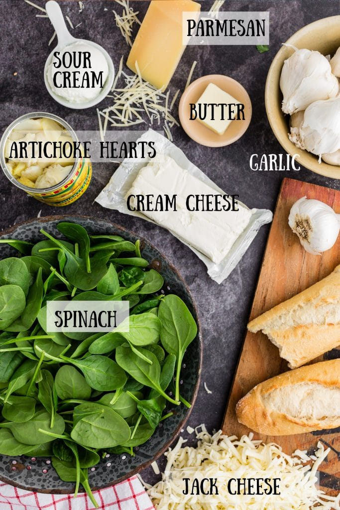 individual ingredients for spinach artichoke dip: cream cheese block, sour cream, artichokes in can, garlic heads, bread, grated cheese, spinach in strainer