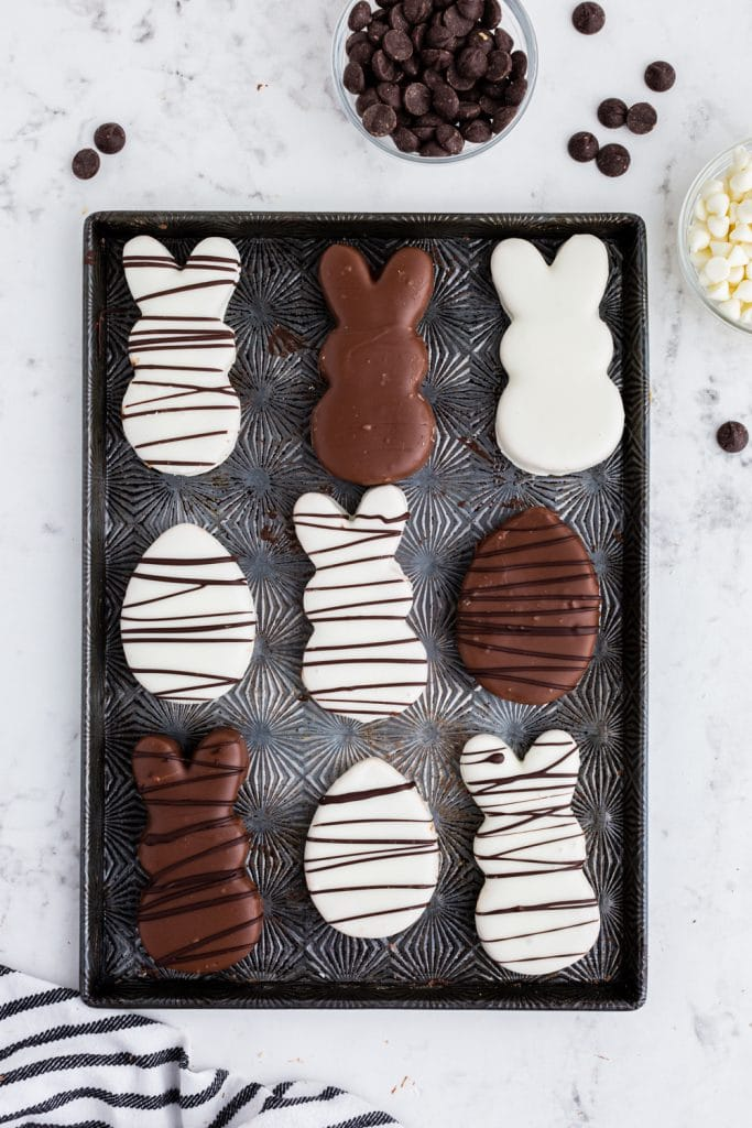 white and milk chocolate bunny and egg shapes with chocolate drizzle set on sheet pan