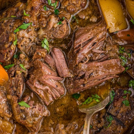 close up of pot roast meat falling apart in gravy with potatoes and carrots