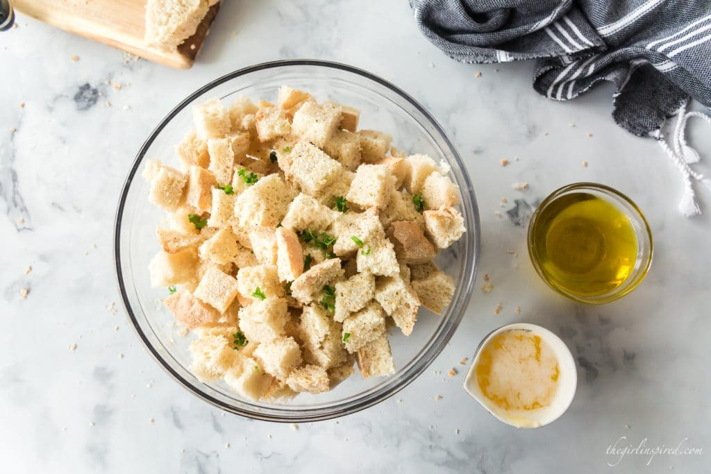 cubed bread and parsley in glass mixing bowl, linen, olive oil, and garlic salt nearby