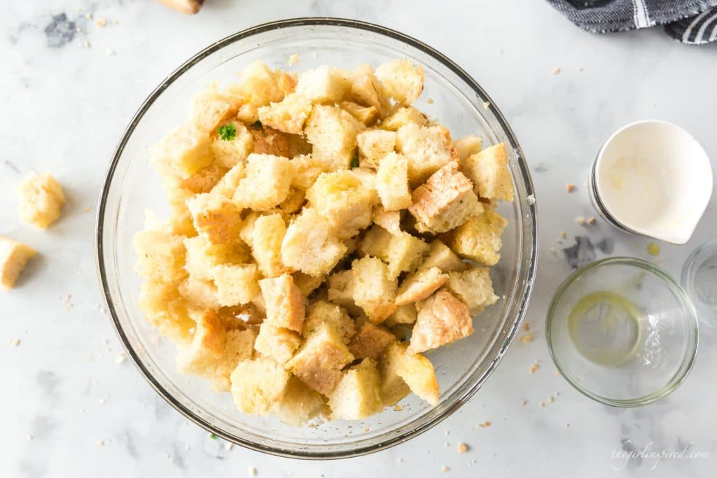 closeup of seasoned bread cubes in glass mixing bowl