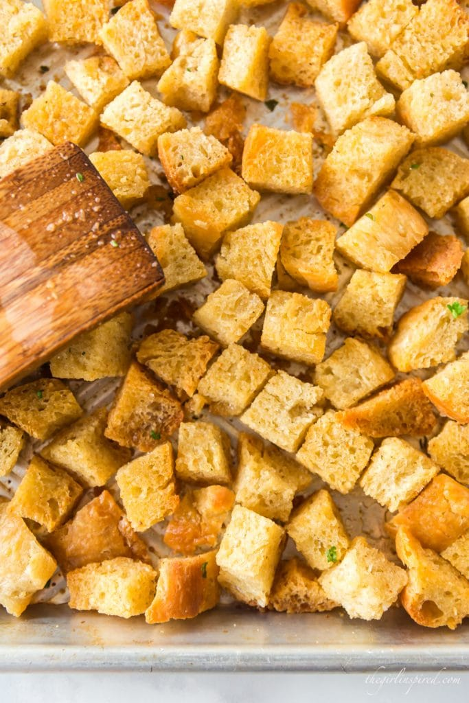 close up of homemade croutons browned and spread out on baking sheet with wooden spatula