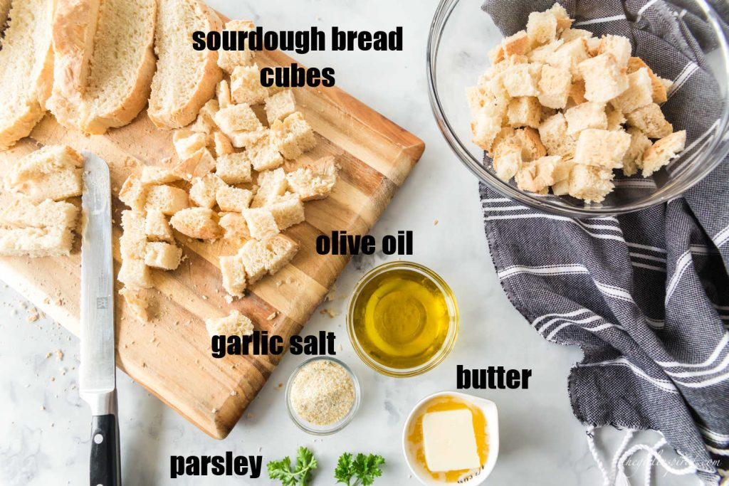 bread on bread board with knife, some pieces cut into cubes and in glass bowl, oil, butter, garlic in little bowls, parsley and linen