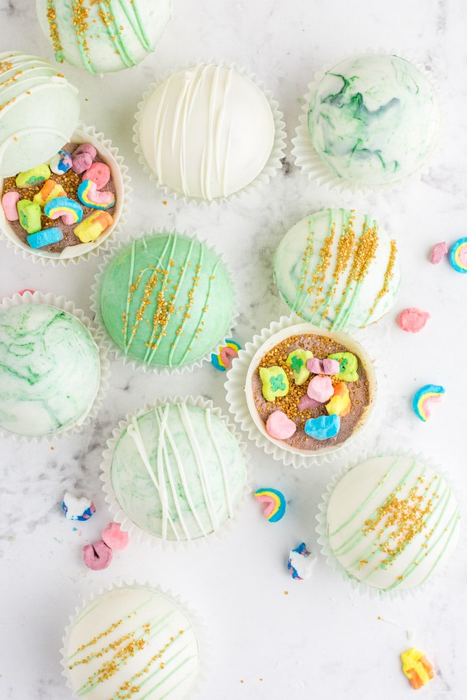 overhead view of green marbled hot chocolate bombs, some open with gold sprinkles and Lucky Charms marshmallows inside, and others decorated with white chocolate drizzle and gold sprinkles.