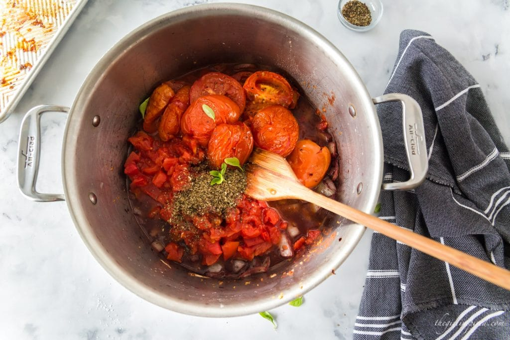 tomatoes and herbs piled in pot, grey linen