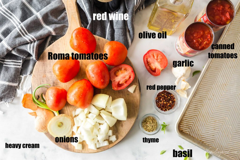 ingredients for tomato bisque - set out on cutting board and counter - tomatoes, onion, herbs, garlic, oil with text overlay