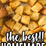 close up of homemade croutons browned and spread out on baking sheet with wooden spatula with text overlay
