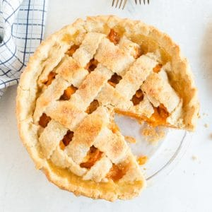 overhead of lattice crust apricot pie with slice of apricot pie removed; blue plate and linen