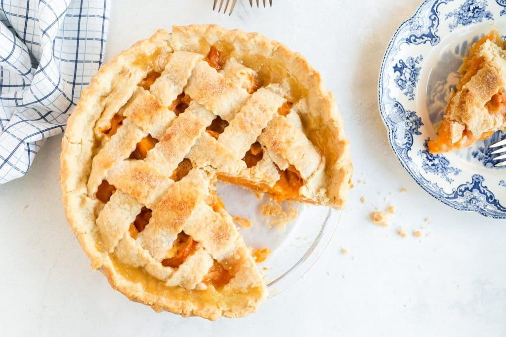 overhead of lattice crust apricot pie with slice removed; blue plate and linen