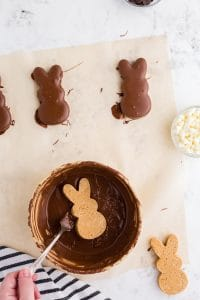 peanut butter bunny being lowered into bowl of melted chocolate