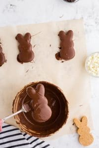 chocolate covered peanut butter bunny lifted from bowl of melted chocolate