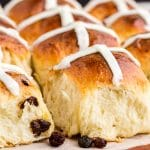 hot cross buns on parchment paper and wooden cutting board with text overlay