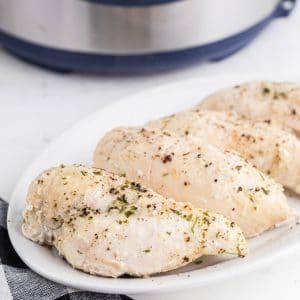 cooked chicken breasts on white platter with instant pot in background