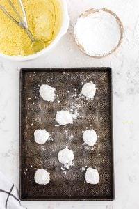 prepared powdered sugar coated balls on cookie sheet