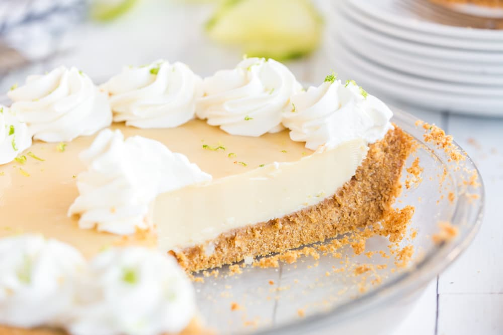 side view of key lime pie in pie plate with slice removed