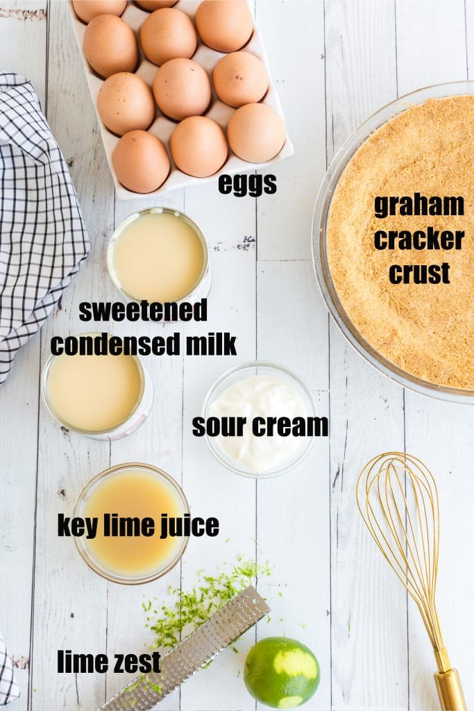 eggs, sweetened condensed milk, lime juice, sour cream, zest, a whisk, and graham cracker crust laid out in individual bowls