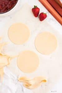 Three pie crust circles on marble countertop