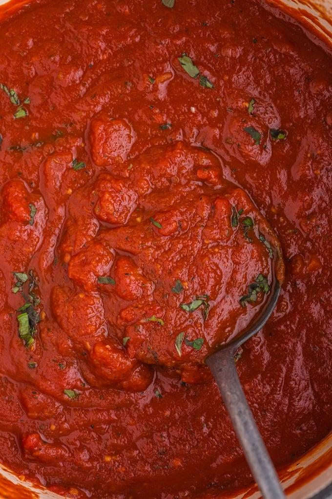 close up of ladle scooping marinara sauce