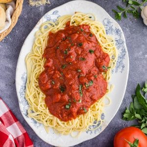 White and blue oval platter filled with Spaghetti and Marinara Sauce, red and white checked linen, tomato, basil