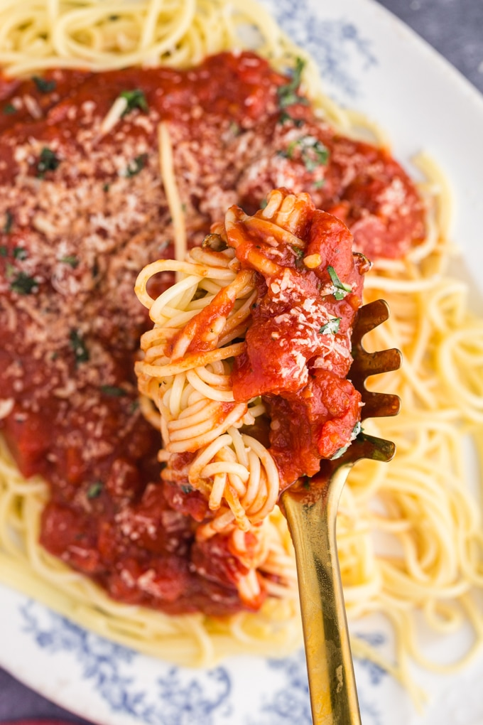 Oval white and blue platter filled with pasta and Marinara Sauce, spaghetti spoon scooping a serving