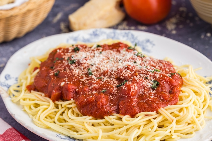 White and blue oval platter filled with Spaghetti and Marinara Sauce , herbs and parmesan cheese on top